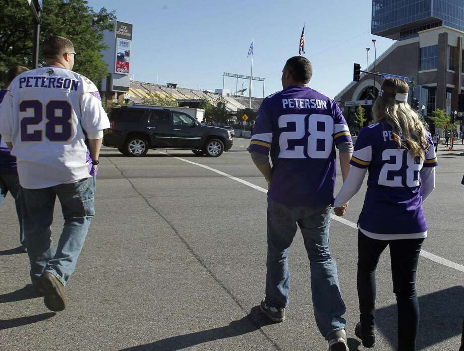 Fans walk to TCF Bank Stadium in Minneapolis wearing Adrian Peterson jerseys before last Sunday's game against New England. Peterson sat out that game because of child abuse charges. Photo: Ann Heisenfelt / Associated Press / FR13069 AP