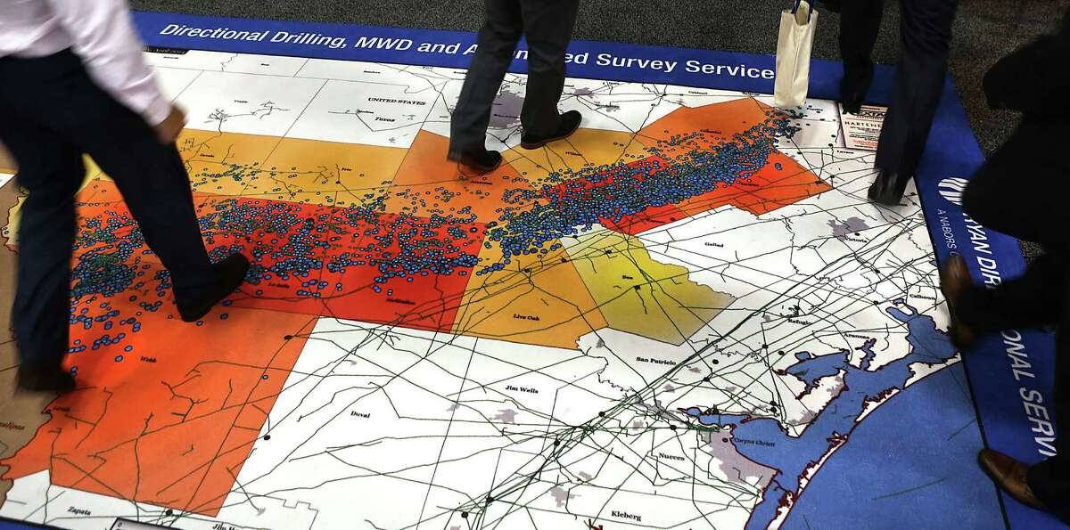 Workers from the oil and gas industry walk across a map showing Eagle Ford well activity in South Texas.