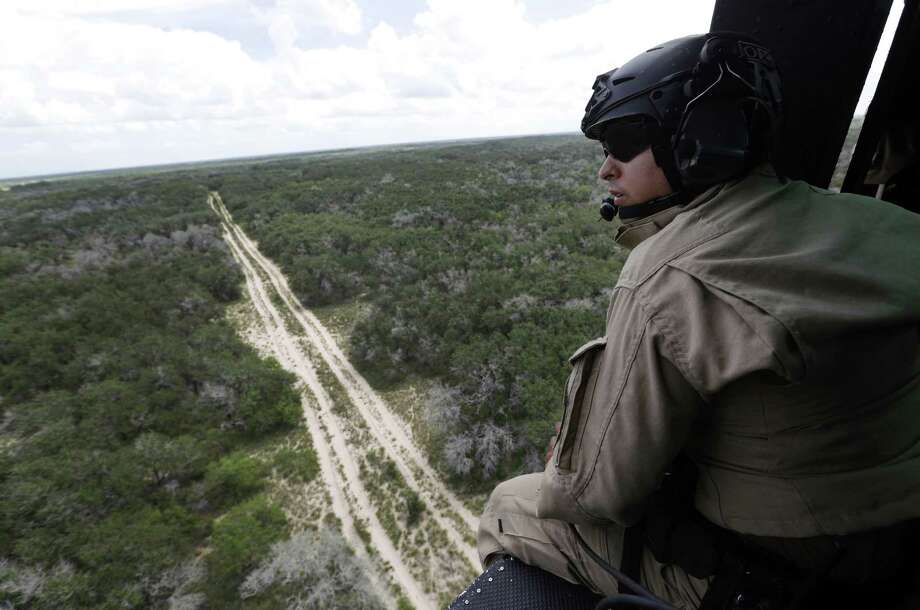 A U.S. Customs and Border Protection Air and Marine agent pears out of the open door of a helicopter during a patrol flight along the Texas-Mexico border near McAllen. Photo: Eric Gay / Associated Press / AP
