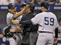 New York Yankees manager Joe Girardi, left, is held back by home plate umpire Rob Drake and third base coach Rob Thomson as he yells at members of the Tampa Bay Rays after Derek Jeter was hit with a pitch by Steven Geltz during the eighth inning of a baseball game Tuesday, Sept. 16, 2014, in St. Petersburg, Fla. (AP Photo/Chris O'Meara)  ORG XMIT: SPD123