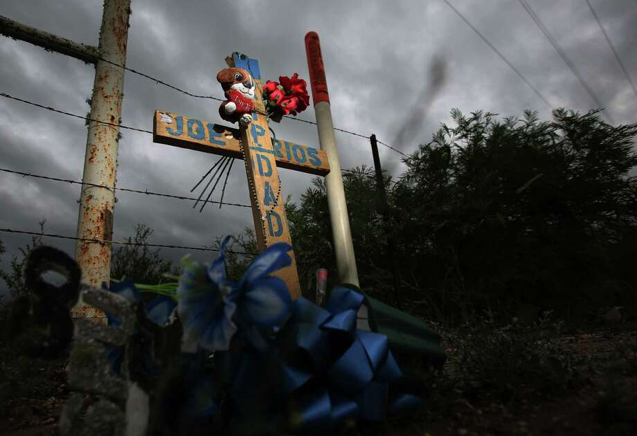 A cross marks where Joe Rios and two other oil field workers died when their van struck a school bus. Photo: Mayra Beltran, Staff / © 2014 Houston Chronicle