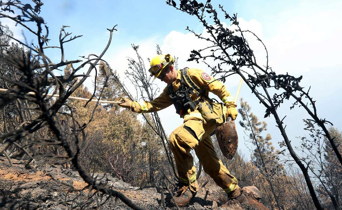 Firefighter Jesse Hadorowski climbs up steep terrain while battling a fire near Pollack Pines, Calif., Monday, Sept. 15, 2014. The fire, which started Sunday has consumed more than 3,000 acres and forced the evacuation of dozens of homes.(AP Photo/Rich Pedroncelli)