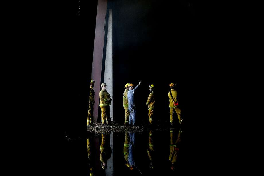 Firefighters inspect the interior of the Roseburg Lumber Mill in Weed, Calif., on Tuesday, Sept. 16, 2014. Parts of the mill, the  major employer in Weed, were damaged in the Boles Fire when it burned through the Siskiyou County town on Monday, Sept. 15, 2014. (AP Photo/The Record Searchlight, Greg Barnette) Photo: Greg Barnette, Associated Press