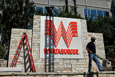 metro - Employees with Keller Custom Signs including Angelo Grizzaffi, right, and Roger Puentes, on top of sign, install the sign for Whataburger's new corporate headquarters building facing 281 in San Antonio on Wednesday, August 5, 2009. LISA KRANTZ/lkrantz@express-news.net