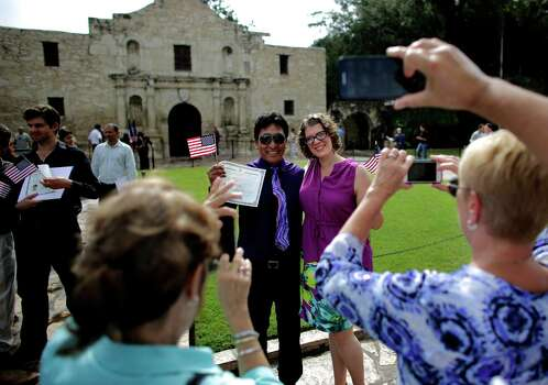 "Friends and family immortalize Austin residents Juan Cuzorla, left with his girlfriend Catherine Jaroschy, right, after Cuzorla was indoctrinated as a naturalized citizen Wednesday, September 17, 2014 in the Alamo Plaza.  ""I'm so excited,"" said Cuzorla, a former teacher from Bolivia.  ""And it's hot!"" After listening to the inspirational speech of antother naturalized citizen who succeeded in achieving their dream, ""I almost felt like crying,"" he said, referencing his own abitions to become a teacher in the United States. Photo: Michel Fortier/San Antonio Expre / San Antonio Express-News"