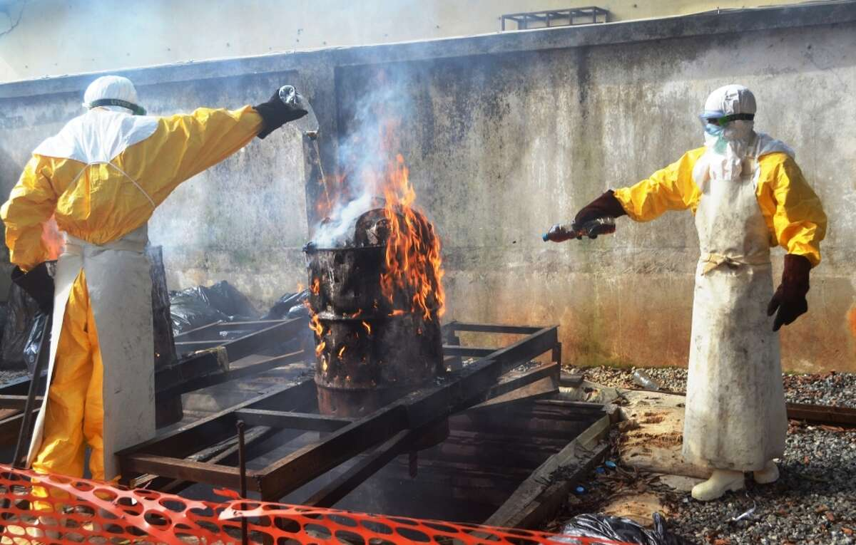Health workers burn used protection gear at the Doctors Without Borders center in Conakry, capital of Guinea.