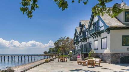 The historic estate at 209 Long Neck Point in Darien features a large stone patio overlooking Long Island Sound.