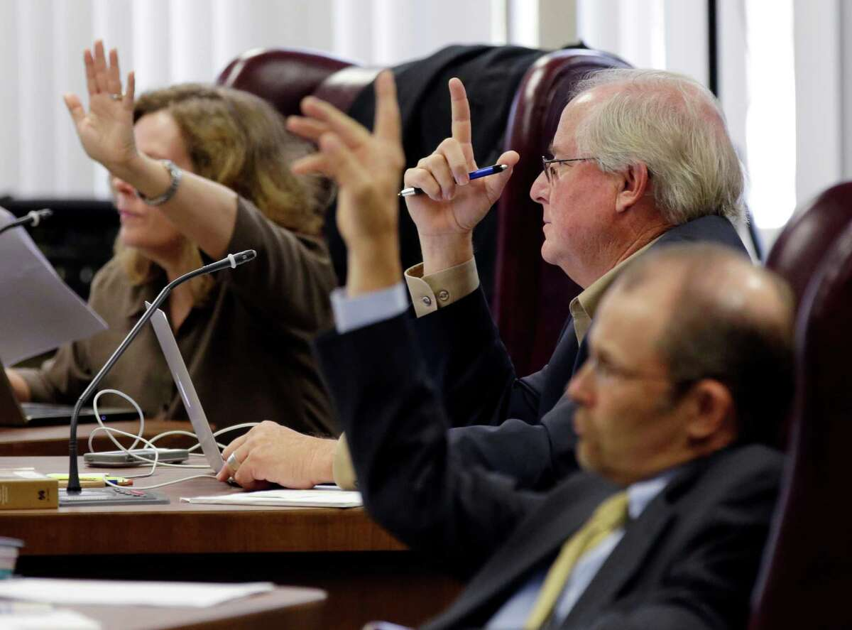 State Board of Education board members, from left, Donna Bahorich, David Bradley, and Thomas Ratliff, raise their hands to ask questions during a public hearing for new textbooks up for adoption and use in classrooms statewide, Tuesday, Sept. 16, 2014, in Austin, Texas. The Texas Board of Education is considering 104 proposed social studies, history, geography and government textbooks that publishers have submitted for approval and use in public schools statewide. (AP Photo/Eric Gay)