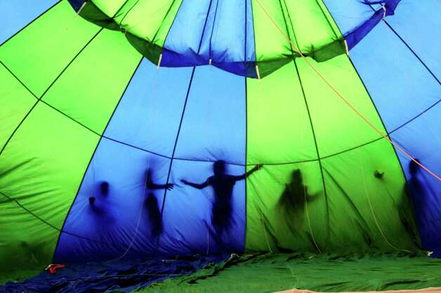 As seen from the inside, children play on the surface of a hot air balloon while it fills with air at the Adirondack Balloon Festival on Thursday, Sept. 20, 2012, at Crandall Park in Glens Falls, N.Y. (Cindy Schultz / Times Union) Photo: Cindy Schultz / 00019355A