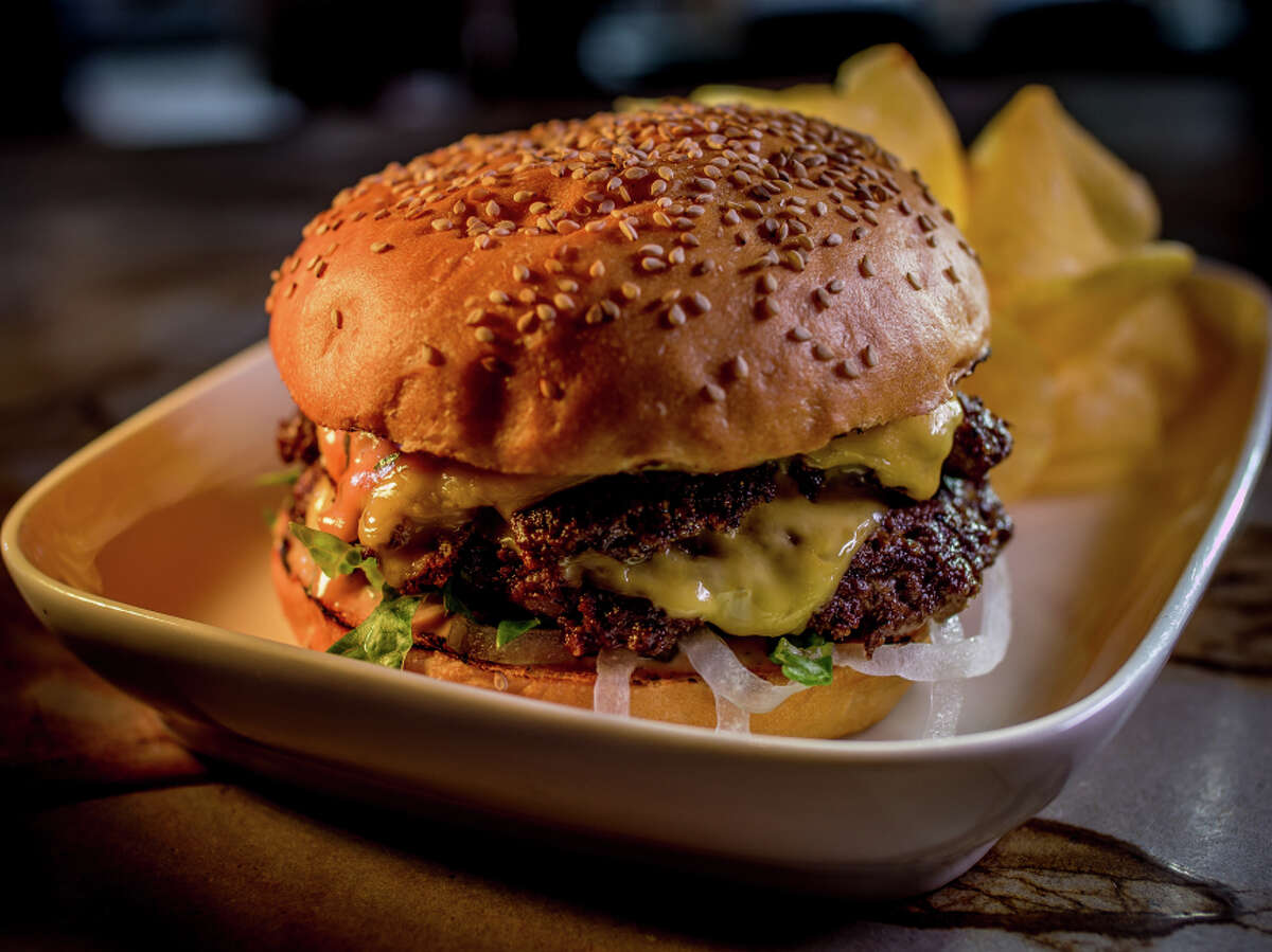 Two well-charred patties make up the beefy bulk of the burger which is served on a toasted sesame bun with chips.
