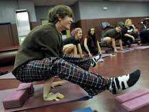Max McKamy, 15, at junior at Bethel High School, assumes a Firefly position in Yoga class Wednesday morning. Stacie Kaye, lead health teacher at Bethel High School, teaches a Hatha Yoga class at the school Wednesday morning, Sept. 17, 2014 in Bethel, Conn.