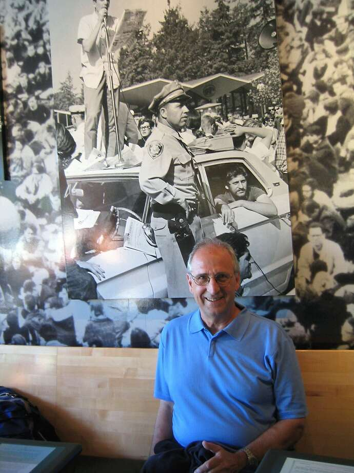 Jack Weinberg, 74, sits in the Free Speech Movement Cafe at UC Berkeley in front of a photo of him in a police car amid a sit-in. Photo: Ravi Agarwal, Jack Weinberg