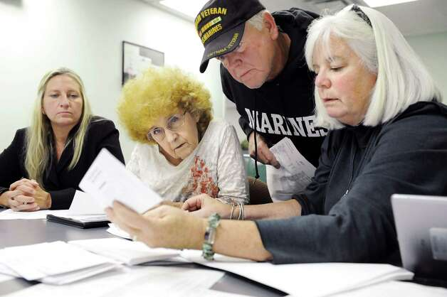 Candidate Howard A. Shafer, center, examines an absentee ballot signature in the 109th Assembly District on Wednesday, Sept. 17, 2014, at Albany County Board of Elections in Albany, N.Y. Joining him, from left, are Jennifer Corona, Carol June-Washington and Pam Robbins. Shafer is running for committee person in Bethlehem District 28. (Cindy Schultz / Times Union) Photo: Cindy Schultz / 00028663A