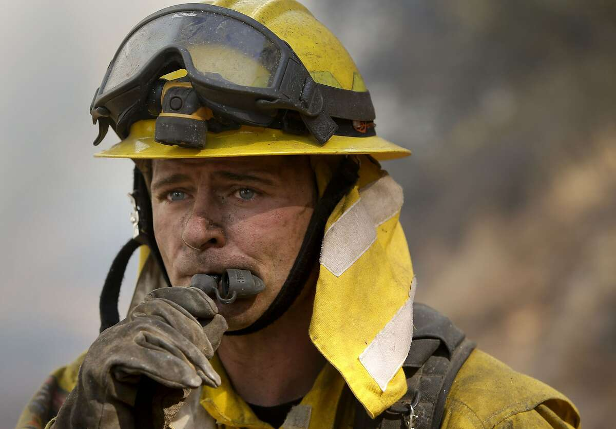 Benjamin Peters with the CalFire Mendocino takes a break for a drink while firefighting fire along highway 50, as firefighters continue to battle the King Fire near Pollack Pines, Calif., on Wednesday Sept. 17, 2014.
