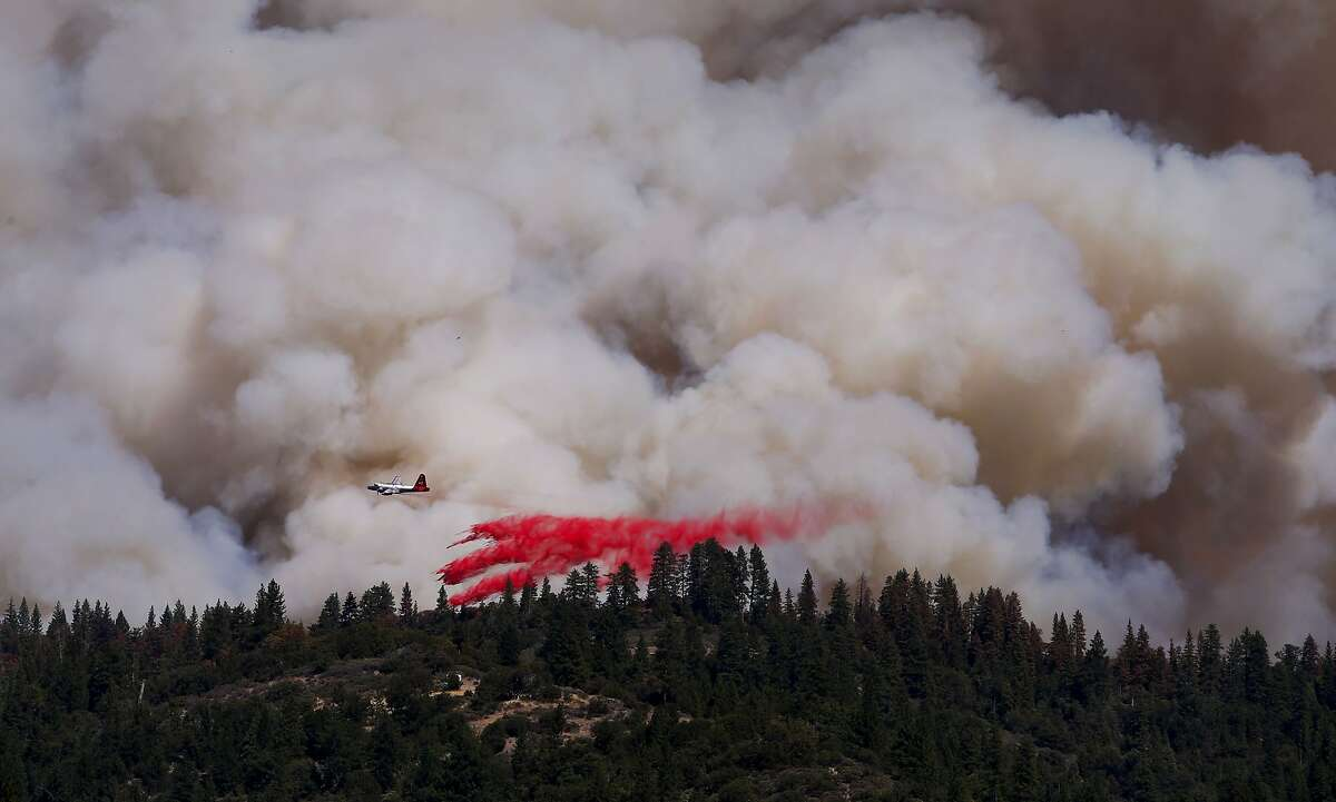 An air tanker lays down fire retardant across a ridge, as firefighters continue to battle the King Fire near Pollack Pines, Calif., on Wednesday Sept. 17, 2014.
