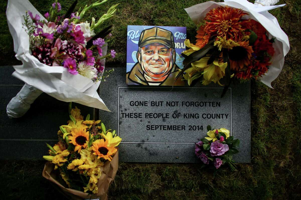 A painting of Gary Campbell is placed on a headstone during a burial ceremony for the remains of 137 unclaimed or indigent people on Wednesday, September 17, 2014 in Renton.