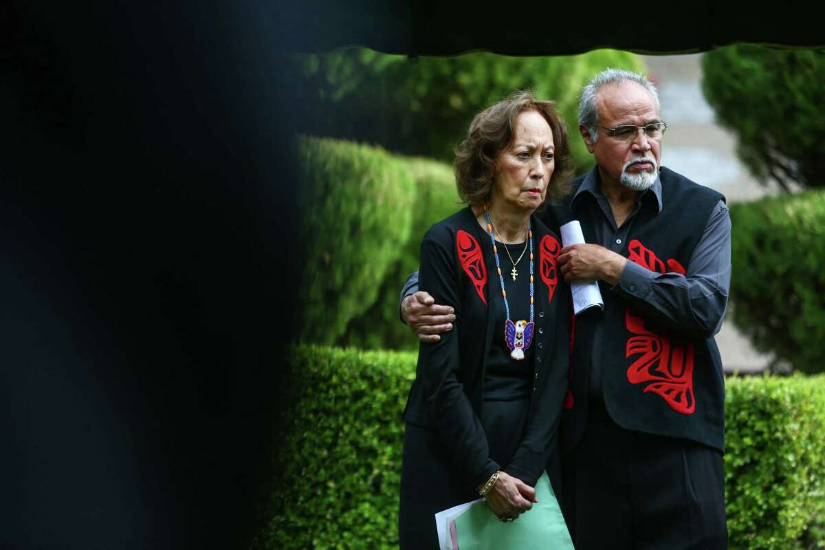Camille Monzon, executive director of the Seattle Indian Center, is embraced by Jack Strong during a burial ceremony for the remains of 137 unclaimed or indigent people on Wednesday, September 17, 2014 in Renton.