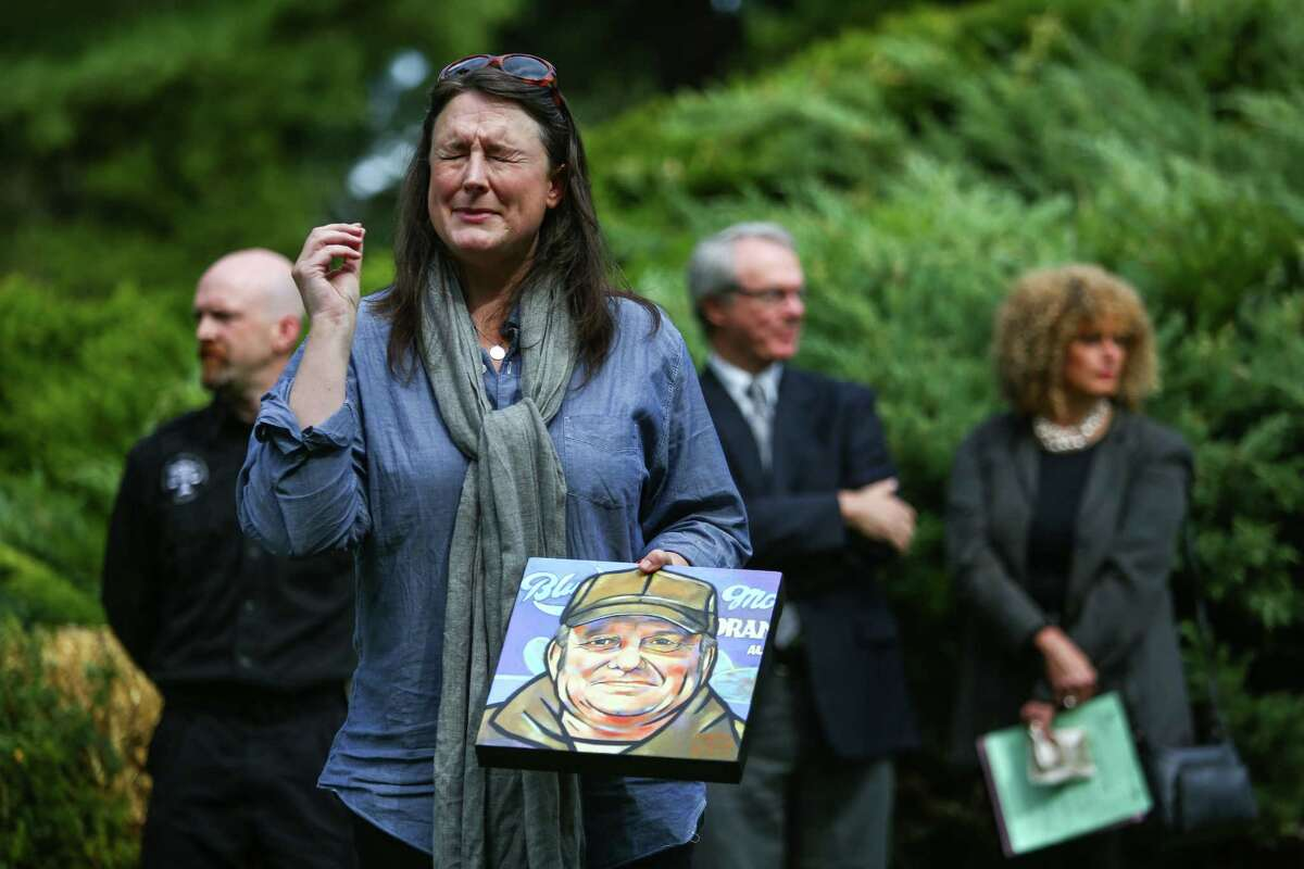 Mary Larson, a nurse at Harborview Medical Center's Pioneer Square Clinic, recalls a story about Gary Campbell as she holds a painting she made of him during a burial ceremony for the remains of 137 unclaimed or indigent people on Wednesday, September 17, 2014 in Renton.