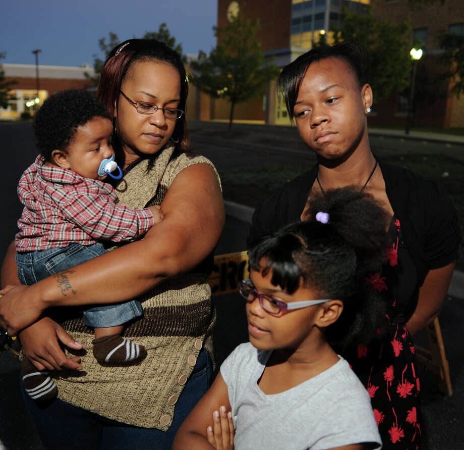 Gloria Byfield stands in front of Waltersville Elementary School with her children Iyzaha, 4 months, Anya Jackson, 13, and Keyana Byfield, 7, in Bridgeport,  Conn., on Wednesday Sept. 17, 2014. Keyana and her big sister Anya were being bothered by two men near the school as they were walking. They asked a police officer in a cruiser for help, but the officer said he was off duty and didn't offer any assistance. Photo: Christian Abraham / Connecticut Post