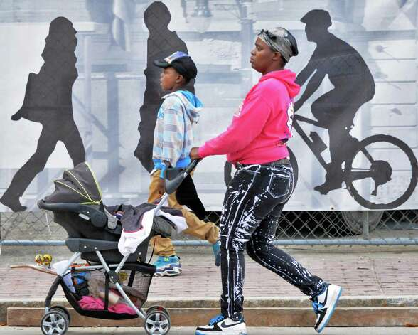 Tiffany Covington of Albany and children Daquan Young, 6, and 9-month-old Amirah Bethea (in stroller) walk past a construction screen in front of the old DeWitt Clinton Building on State Street Wednesday Sept. 17, 2014, in Albany, NY.  (John Carl D'Annibale / Times Union) Photo: John Carl D'Annibale