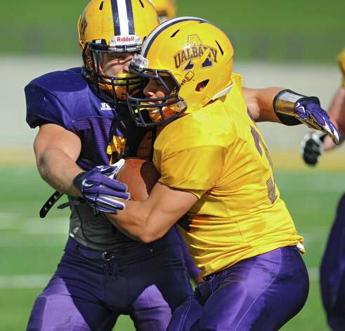UAlbany linebacker Michael Nicastro, left, makes a tackle during football practice on Wednesday, Sept. 17, 2014 in Albany, N.Y. (Lori Van Buren / Times Union) Photo: Lori Van Buren / 10028658A