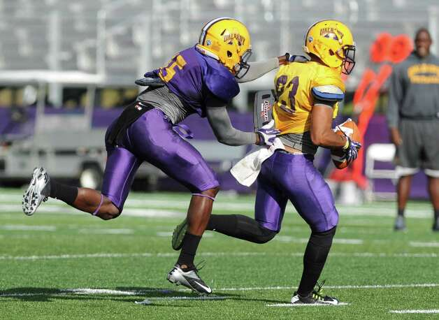 UAlbany safety Rayshan Clark, left, makes a tackle during football practice on Wednesday, Sept. 17, 2014 in Albany, N.Y. (Lori Van Buren / Times Union) Photo: Lori Van Buren / 10028658A