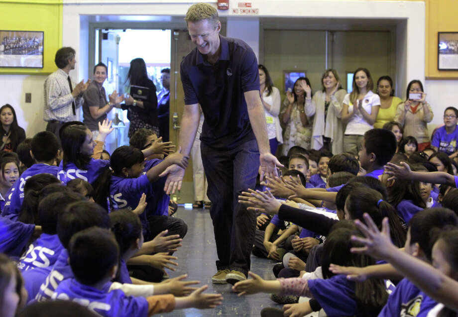 "Warriors head coach Steve Kerr brings low-fives and high enthusiasm for reading to students at Longfellow Elementary School in San Francisco in conjunction with the ""Read to Achieve"" program. Photo: Paul Chinn,  Staff / The Chronicle / ONLINE_YES"