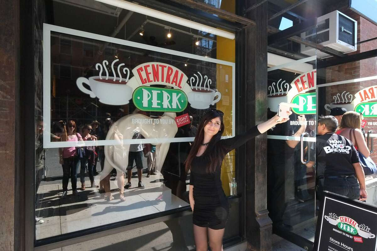 """A woman takes a selfie in front of the pop-up """"Central Perk"""" coffee shop setup in New York's SoHo neighborhood to celebrate the 20th anniversary of the television sitcom """"Friends."""""""