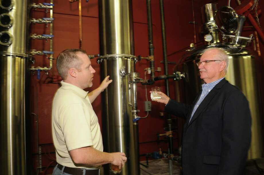 Yellow Rose Distilling co-owner Ryan Baird, left, chats with Lyndon Sommer during a tour of the  warehouse.Yellow Rose Distilling co-owner Ryan Baird, left, chats with Lyndon Sommer during a tour of the  warehouse. Photo: George Wong / Freelance