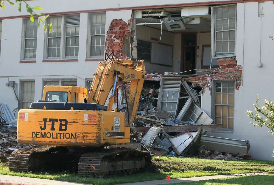 A parked excavator sits outside Wheatley High School as community leaders protest the demolition of the historic Fifth Ward campus Sept. 1.