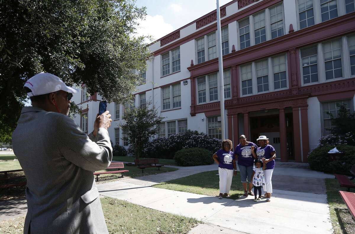 Pauline Ransom-Franklin, left, Kathy Blueford-Daniels, center, and Sandra Whittaker, with her great-niece Jade Hardy, 2 1/2 get their photo taken by Greg Stuart in front of the old Wheatley High School, built in 1927, just before they and other members of the Historic Wheatley/EO Smith Preservation Coalition held a press conference outside the school at 1700 Gregg Street in late August.