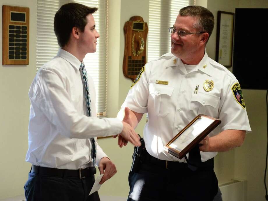 """Police Chief Leon Krolikowski presents a """"Civilian Service Award"""" Wednesday, Sept. 17, 2014, to Grayson Cordes, an assistant manager at Walgreens, 36 Pine St., New Canaan, Conn., who helped foil an attempted fraud at the store July 21, 2014. Photo: Nelson Oliveira / New Canaan News"""
