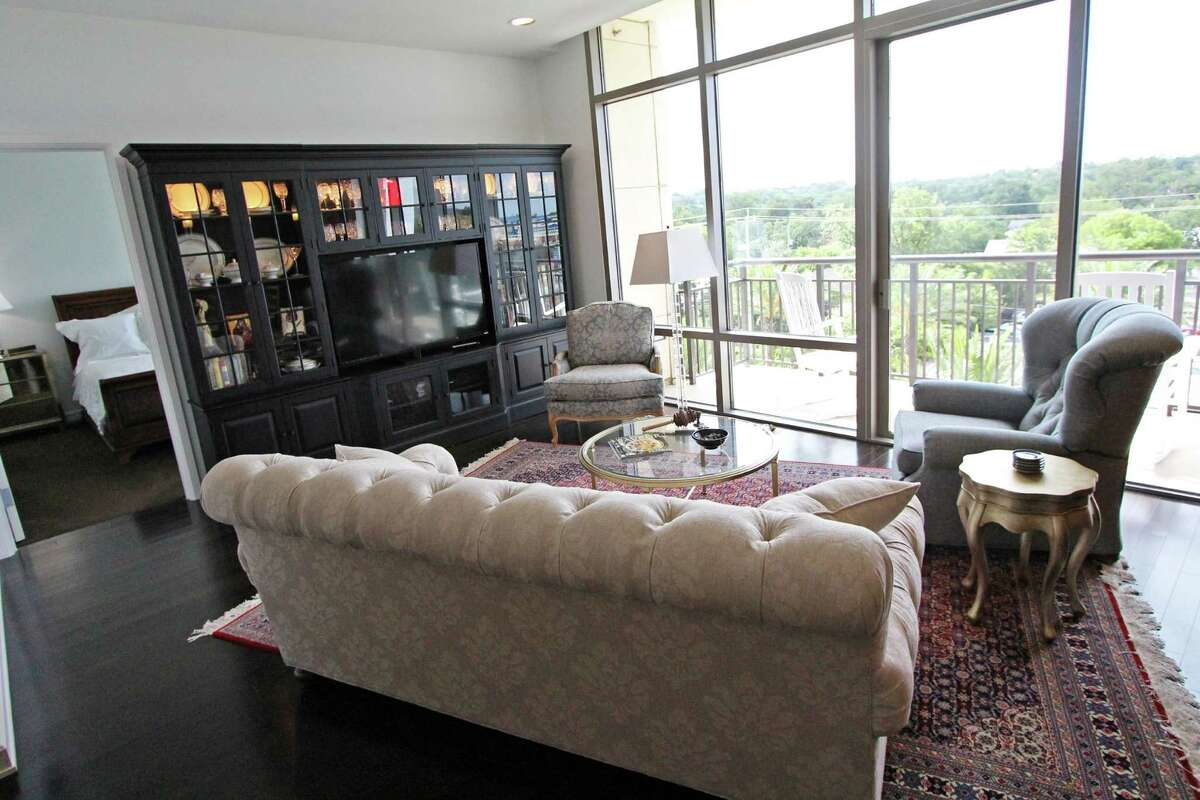 A rug that Belinda Pustka brought back from China is angled in the living room, anchored by a new couch and two chairs. One wall of the living room is all glass, windows and doors, offering a great view of downtown San Antonio. The wall unit holds China and mementos of her travels.