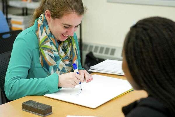 Megan Reilly tutors students in Algebra I at Stamford High School on Thursday, September 18, 2014.