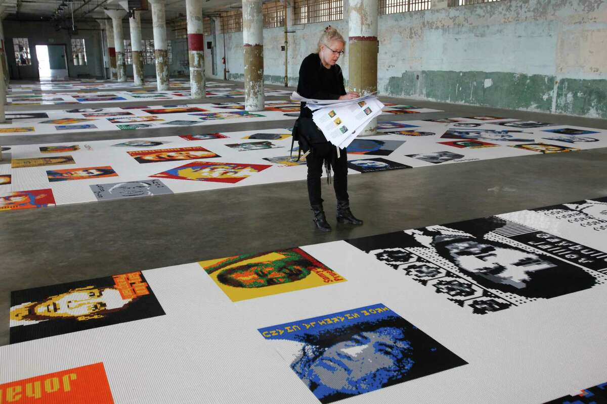Designer Jen Burke cross references interpretive material for an informational binder for one of the art pieces featuring 176 portraits of prisoners of conscience made out of Legos as part of the show @Large: Ai Weiwei on Alcatraz.