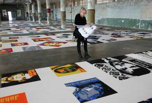 Designer Jen Burke cross references the interpretive material for an informational binder for one of the art pieces featuring 176 portraits of prisoners of conscience made out of legos as part of the upcoming show @Large: Ai Weiwei on Alcatraz in the New Industries Building Sept. 11, 2014 on Alcatraz Island in San Francisco, Calif. The @Large: Ai Weiwei on Alcatraz will feature seven pieces and will run September 27, 2014 Ð April 26, 2015.