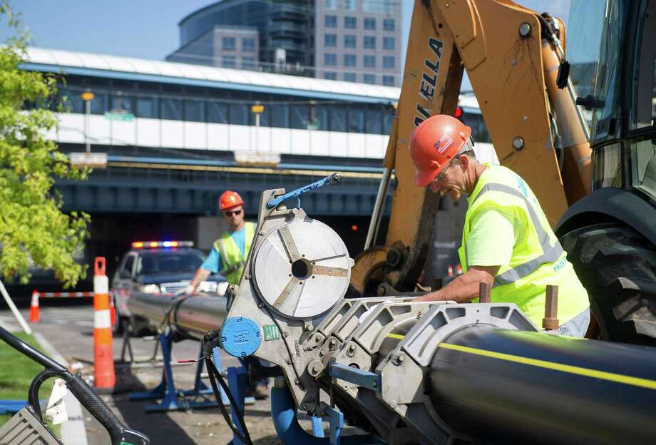 Danella Construction employees join two sections of pipe as they work to lay a pipe for natural gas for the Building and Land Technology buildings at the intersection of Washington Blvd. and Henry Street near the Stamford Transportation Center in Stamford, Conn., on Thursday, September 18, 2014. Photo: Lindsay Perry / Stamford Advocate