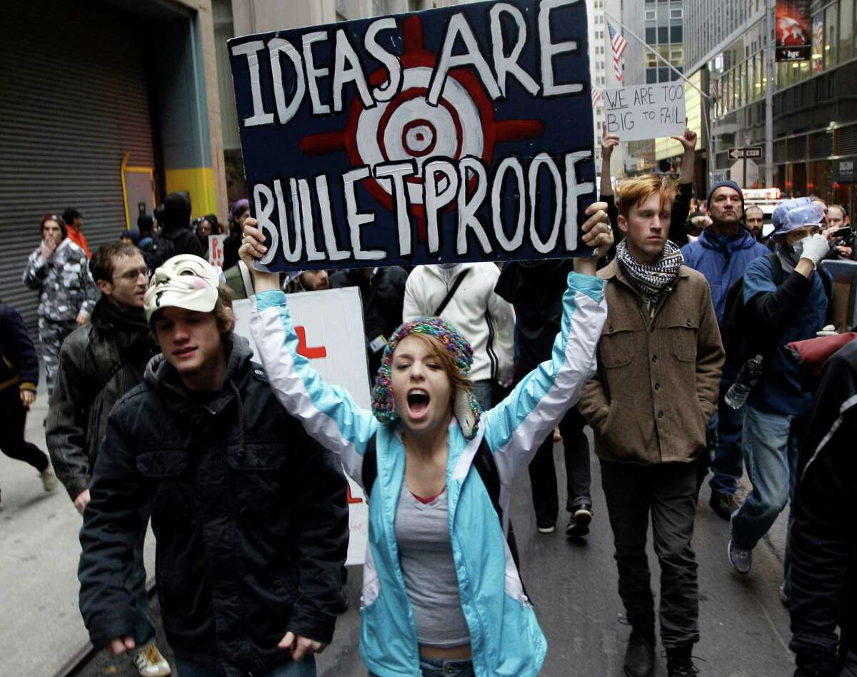 In this Nov. 17, 2011 file photo, demonstrators affiliated with the Occupy Wall Street movement march through the streets of the financial district in New York. Income inequality is having a moment. Some of the wealth gap's earliest champions - a group of bearded and tattooed protesters who called themselves Occupiers - made the problem famous in 2011 when they took up residence in a small granite plaza near the New York Stock Exchange. Two and a half years later, long after Occupy Wall Street fizzled out, income inequality is finally being taken seriously by world leaders. (AP Photo/Mary Altaffer, File)