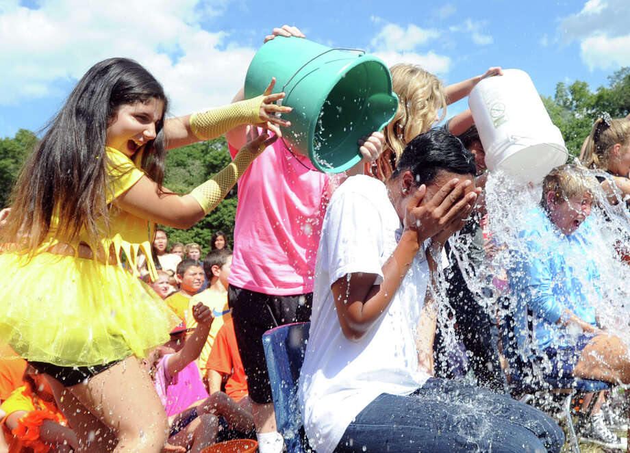 Central Middle School eighth grader, Cosette Leonard, 12, at left, dumps ice water on the head of Shamain Johnson, a CMS asst. principal, as other students dump water on the head of CMS Principal Shelley Somers, right, during the Ice Bucket Challenge at the school in Greenwich, Conn., Thursday, Sept. 18, 2014. The event was a fundraiser for a student who was seriously injured in a recent bicycle accident. Photo: Bob Luckey / Greenwich Time