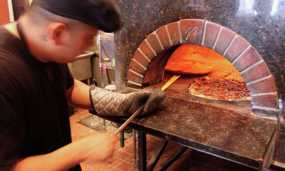 In this Sept. 5, 2014 photo, a cook prepares pizza at Coalfire pizzeria in Chicago. Chicago is one of a handful of cities across the country, like Boston, Milwaukee and New York, with companies that offer tours of the local pizza scene. (AP Photo/Caryn Rousseau) ORG XMIT: RPCR404 Photo: Caryn Rousseau / AP