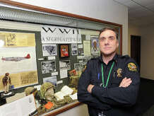 "Greenwich Police Officer Bill Romanello in front of the ""WWII, a Segregated War"" display that he and the Connecticut Combat Team, a group of amateur military historians, put together at Greenwich Town Hall, as seen Friday, Nov. 22, 2013."