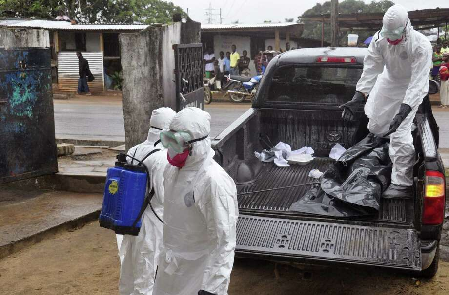 Health workers move the body of a possible Ebola victim in Monrovia, Liberia. Any notion of U.S. nonintervention in the epidemic is both unrealistic and dangerous. Photo: Abbas Dulleh / Associated Press / AP