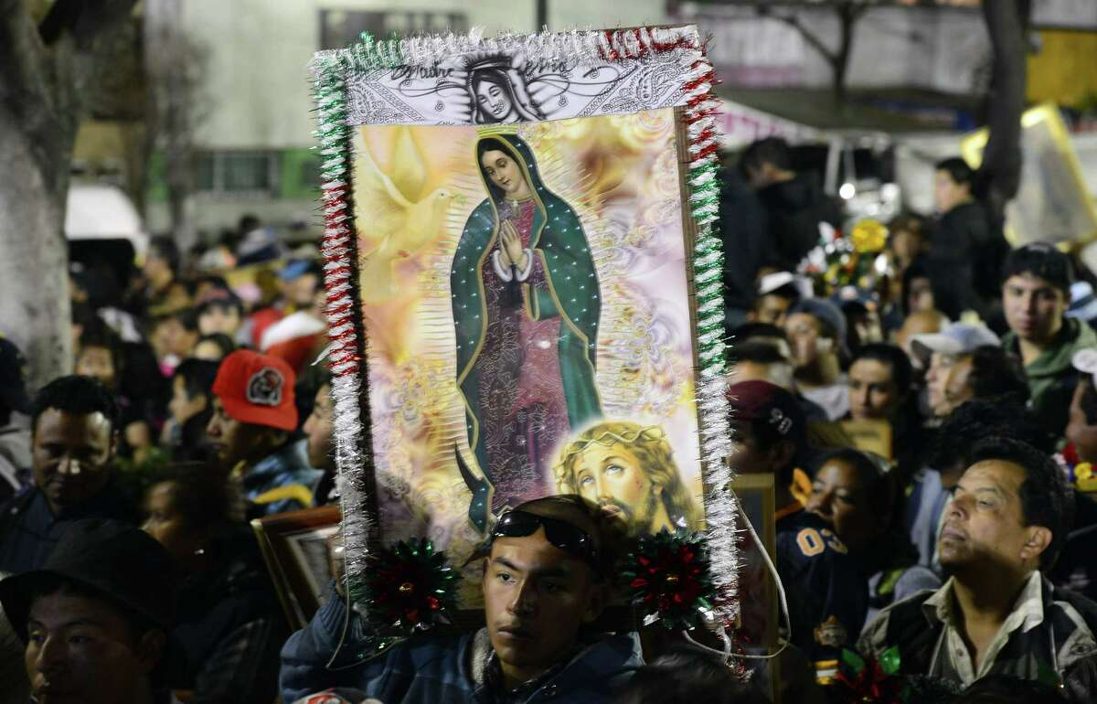 Pilgrims hold an image of the Virgin of Guadalupe in Mexico City. A reader carried an image of the Virgin in his billfold, and it was its loss that caused him the most sorrow. His story has a happy ending.