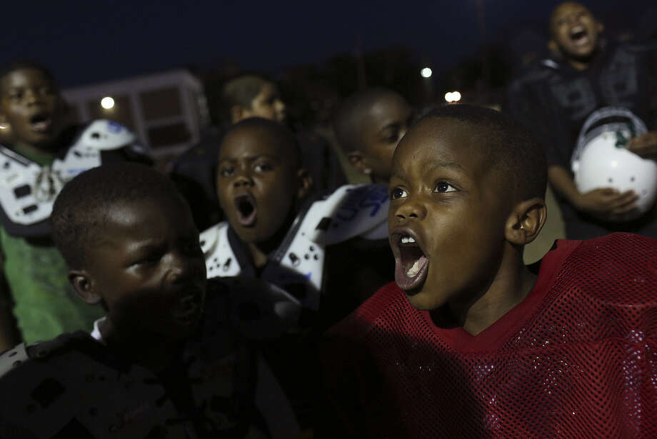 Keith Scott Jr. (right), 8, a member of an East Side youth football team, chants with his teammates. The team received a generous donation recently, and a reader is happy for the kids but not about their team name. Photo: Lisa Krantz / San Antonio Express-News / SAN ANTONIO EXPRESS-NEWS