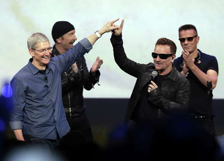 """Apple CEO Tim Cook (left) greets Bono from U2 after an Apple event this month in Cupertino, Calif. Apple unveiled a new Apple Watch, the iPhone 6 and ApplePay, and U2 sent iTunes customers a free download of """"Songs of Innocence."""" Photo: Marcio Jose Sanchez / Associated Press / AP"""