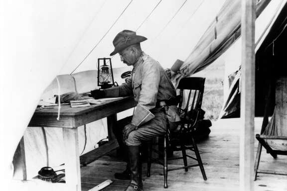 Theodore Roosevelt working at a desk inside his tent in San Antonio during the training of the Rough Riders. FILE PHOTO