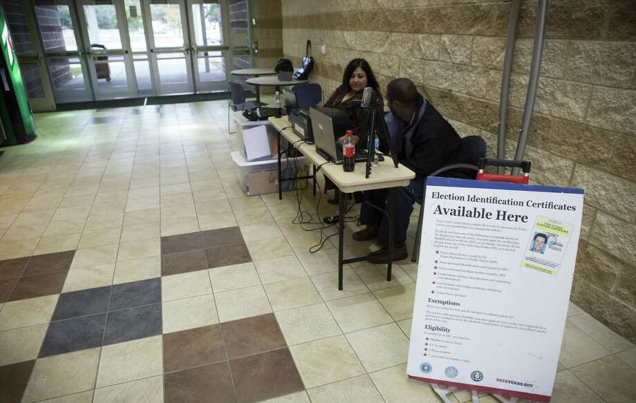 A DPS stand provides voter identification certificates in Houston. By reacting to the motivations of some unethical politicians, upright citizens make a broad-brush condemnation of a good law. Photo: New York Times File Photo / NYTNS