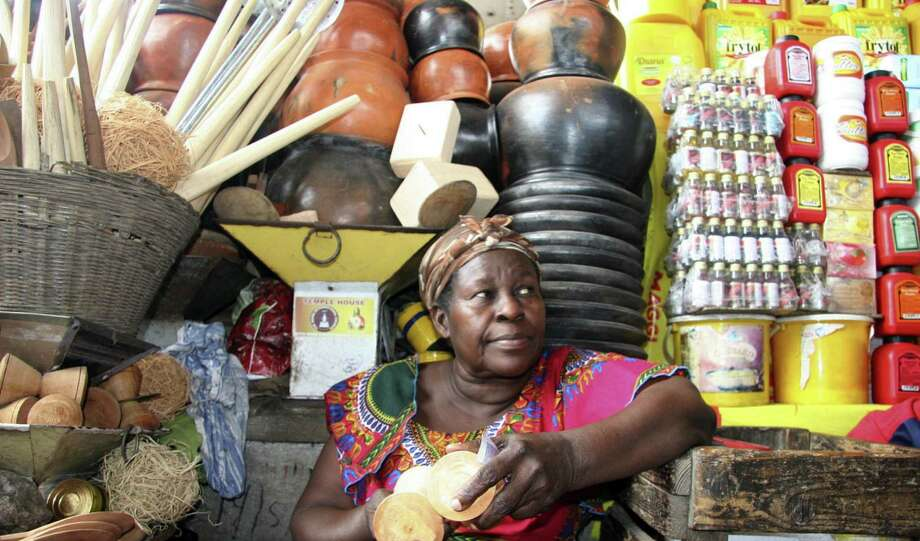 Elizabeth A. Konada, 59, offers food items and housewares at the huge Kaneshie Market in Accra. Photo: Susana Hayward / For The Express-News