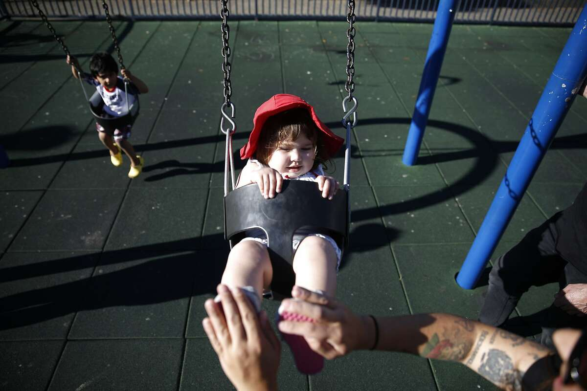 Adriel Lively (right) pushes her daughter Ann Bruton (center), 21 months, on a swing at a playground at Civic Center Plaza on Wednesday, September 17, 2014 in San Francisco, Calif.
