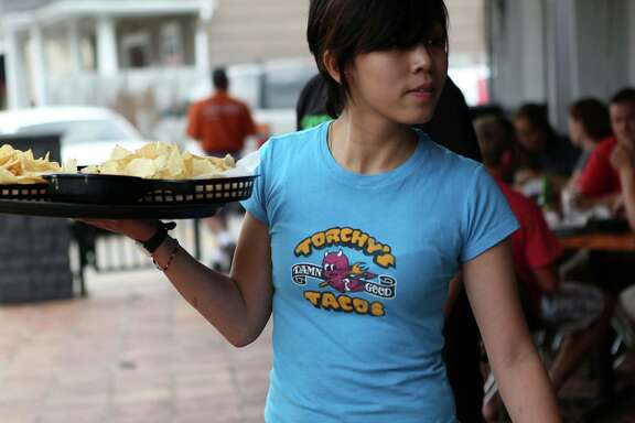 Vivian Nguyen delivers chips at a Torchy's Tacos on Shepherd.  Torchy's has four restaurants in the Houston area.